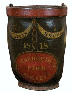 """Leather Fire Bucket - Early 19th c. leather fire bucket, original green and red paint, """"No. 1, Calvin Bruce"""", in a swag and tassel curtain with gold chain, """"1818"""", red oval with """"Energetic Fire Society"""", missing the handle, 12″ h, 8 1/2″ dia, (ex. Fertig collection)."""