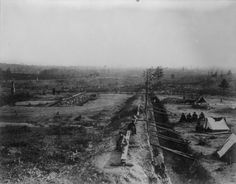 THE TYPICAL HEAD-LOG WITH SKIDS—SHERMAN'S DEFENSE BEFORE ATLANTA If a shell drove back one of the head-logs in this photograph, it might crush and maim the soldiers in the trenches but for the skids across the trenches. The head-log was placed on top of the earth parapet, with a space left under the log to permit the men to fire.