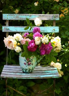 Shabby chic wooden chair with a colorful array of flowers in a painted watering can. Pink, robin's egg blue chipped paint, rustic.