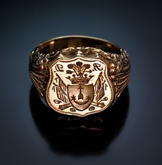 An Antique Signet Gold Ring circa 1840. A very rare antique Russian armorial seal ring with the crest of the Yaminsky family. The shaped shield of the ring is centered with the Yaminsky coat of arms, surrounded by military trophies – banners, cannons, cannonballs, and swords. The shoulders are embellished with stylized floral decorations cast in high relief. The ring is marked with 72 zolotnik old Russian gold standard (18K) and Moscow assay stamp. Height – 3/4 in. Weight – 28.2 g. Ring sz…