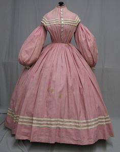 "Spectacular 1860's Civil War Era Pink Cotton Daytime Ensemble: one piece dress ; mother of pearl buttons ; bust 30, waist: 22, skirt length of 38, hem width 165"". There are scattered stains with the largest ones in front. There is fading to the shoulder areas, underarm stains and some small holes. If this color is stay fast you could wash the garment and possibly soak out the stains. bodice lined; skirt unlined; cartridge pleated."