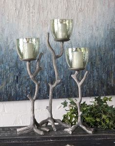 Uttermost Desi Candleholders. Antiqued, Textured Aluminum With Translucent Green Glass. White Candles Included. Sizes: Sm-6X16X5, Med-8X17X8, Lg-8X22X7. Available at Sacksteder's Interior's for home decor and interior design!
