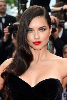 Adriana Lima ose le look femme fatale : side hair légèrement ondulé, cat eye et rouge à lèvres flamboyant !