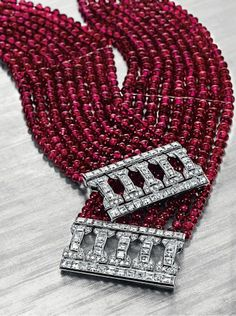 CARTIER - A Pair of Art Deco Ruby Bead and Diamond Bracelets, Circa 1925. Designed as nine strands of ruby beads, joined by a square and single-cut diamond openwork clasp of geometric design, mounted in platinum, with French assay mark and maker's marks Signed Carter, France, numbered. #Cartier #ArtDeco #bracelet