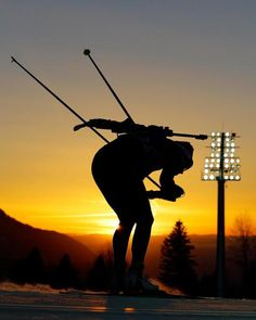 An athlete is silhouetted as the sun sets during a biathlon training session at the 2014 Winter Olympics