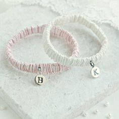 A charming little silk wristband with a sterling silver initial charm in the initial of your choice.Available in ivory, white or pink with a sterling silver pendant. This little silk wristband makes a perfect little christening gift or present for a newborn baby keepsake. The silk matches our gowns and dresses perfectly and the wristband bracelet has elastic through it for comfort. Each wristband comes to you beautifully packaged in a little gift box hand tied with a pretty satin…