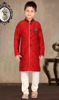 Red shade jacquard kids sherwani featuring jacquard foliage patterns spread all over. Beads, zardosi, stones heavily ornated collar, buttons and foliage motifs on one side of the chest that intensifies the look. #HandsomeLookShervaniDesignForBoys