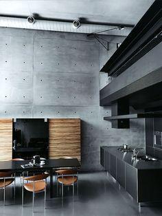 cocina moderna color negro, isla central con fregadero y zona de cocción, frente para horno y microondas con muebles de almacenaje, suelo microcemento, paredes hormigón visto