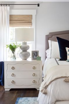 Modern yet classy bedroom design with white decorative dresser and grey headboard | Studio McGee