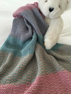 Colorful stripes in garter stitch give this baby blanket cheer and warmth. While the pattern looks complicated, every row is the same simple knit-purl sequence. The fun is in the selection of colors for the stripe. I chose five rainbow colors, you're welcome to use more or fewer.