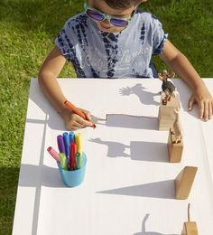 Let shadows be your child's guide for this activity. In the morning (8 a.m.) or late afternoon (4 p.m.), place a table in a sunny spot where long shadows will be cast. Unroll paper (Easel Paper Roll, $14; alexbrands.com) along one side of the table,
