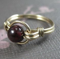 Wire wrapped ring in 14k yellow gold filled wire with 6mm garnet in O Loop design. This ring is made with my O-loop design in 14k gold-filled wire and features a deep reddish-purple garnet (approximately 5-6mm). Also available in 14k Rose gold-filled wire. All sizes available, #rosewirerings #wireringsrose #wireringsdesigns