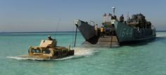 Humvee launches from landing craft utility on an Arabian Gulf beach