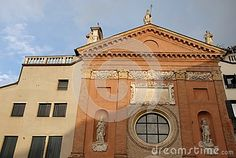 Photo made at the simple facade of the church in the Piazza dei Signori in Padua in the Veneto (Italy). At the center of the picture you see a large circular window with the wide railing that divides it into nine parts, flanked by two statues in their niches, over a plate of stone illuminated by the setting sun. Beside the church there are two buildings, one on the left, cut by the sun, he has the windows closed.