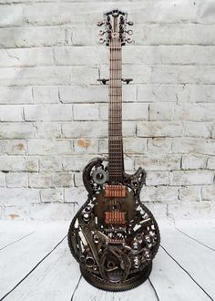 Metal scrap art guitar sculpture of a full size Les Paul electric guitar. unique sculpture, hand crafted eye catching piece of art. Each one is 100% original and unique.    The guitar has been hand crafted out of various scrap metal items tig welded together and clear lacquered for protection. Full size. Can be mounted on a normal guitar stand or a stand like in the picture can be made.   Dimensions: Weight 10.5 Kg 1020 mm high 350 mm wide 100 mm deep  This one is for sale but any style can…