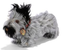 A STEIFF STANDING SKYE TERRIER, (1312,0), long gray and black mohair, brown and black glass eyes, brown stitching, inoperative squeaker, red collar, FF button with remains of yellow cloth tag and chest tag, 1930s --8½in. (22cm.) long (one ear a little sparce)