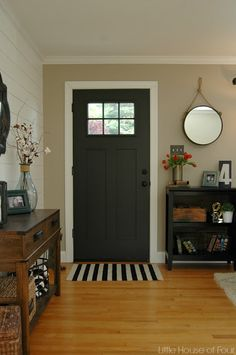 A painted front door and inexpensive home decor pieces transformed this basic entryway.
