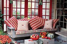 Bright Red Porch - 80 Breezy Porches and Patios - Southernliving. Red is the defining color throughout this outdoor space. Using a single hue is an easy way to tie the look together. Extra pillows add color and comfort.  Outdoor Rooms
