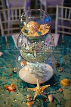 As attendees walk down the stairs they submerge under the sea two glass boxes with coral reef deco inside create an entryway for guest and opens up the dining area and dance floor ruffled aqua blue liens cover the circle table long rectangle glass table Mermaid Theme Birthday, Little Mermaid Birthday, Little Mermaid Parties, The Little Mermaid, Mermaid Baby Showers, Baby Mermaid, Baby Shower Mermaid Theme, Beach Bridal Showers, Mermaid Wedding