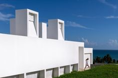 White concrete walls and chimneys feature in this seaside residence that was designed by Fuster + Architects to be able to endure tropical storms. Weather Hurricane, Hurricane Shutters, Capsule Hotel, Concrete Houses, Concrete Walls, Steel Columns, White Concrete, Level Homes, Wooden Decks