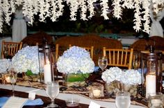 Beautiful Tropical White Wedding Reception Table Arrangements For Your Destination Wedding in Hawaii. Hydrangeas with ti leaf wrapped vases plus leis