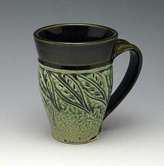 Artfully carved leaves adorn this green and black mug by pottery Ira Burhans.  Handmade in the USA!