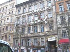 Oost vs. West: een typisch Oost-berlijns gebouw dat nu opgeëist is door street-artists. zij verzetten zich tegen moderne problemen, en dus ook tegen het corrupte kapitalisme.