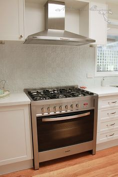 Pressed tin splashback/backsplash powder coated for durability and for use behind the stove. Love that there is not one single scrap of grout in this room!
