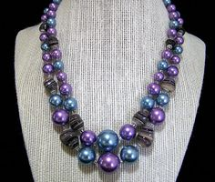 Mid Century 2 strand graduated beads necklace Blue and purple round faux pearl beads, with irregular swirled purple art glass beads Strands are 16.5 and 17.5 inches long. This can be worn up to 2 inches shorter Lovely colors for spring and summer Hook clasp is signed Japan Good condition I specialize in vintage beaded jewelry, please visit my shop to see more International buyers welcome, overcharges are refunded Flat rate priority shipping is optional 42917   Want to see more great…
