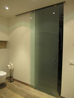 Ceilinghigh glass sliding bathroom door.