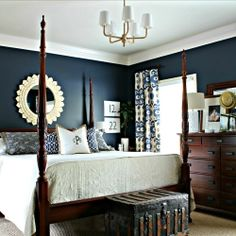 Dark walls and brown furniture light bedspread and a few accents