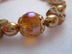 A BEAUTIFUL ELEGANT SHELL AND ACRYLIC BEADED BRACELET.  THIS BRACELET IS AN EASY ON/ EASY OFF STRETCH BRACELET WITH CREAM COLORED SQUARE SHELL BEADS THAT HAVE AMBER TONES. ...