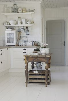 FARMHOUSE – INTERIOR – early american decor inside this vintage farmhouse seems perfect such as small simple rustic island, crisp white cabinets, open shelving, plank ceiling, gray door. Cozinha Shabby Chic, Shabby Chic Kitchen, Country Kitchen, Rustic Kitchen, Cottage Kitchens, Home Kitchens, Kitchen Dining, Kitchen Decor, Kitchen Grey