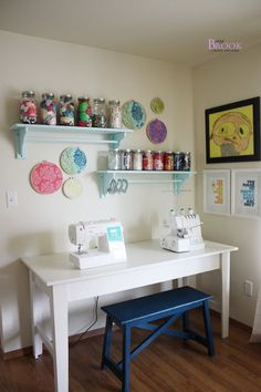 Sewing table set up.  Like the shelves above the table and kid's art on the wall