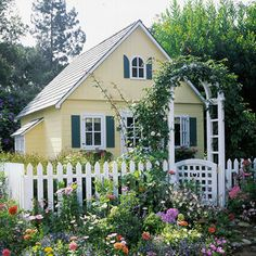 Captivating Cottage~~~~A combination of colors and materials create an unusually realistic Garden shed. Part of the appeal? The fence and arbor, details picked up from the designs found in full-size cottage gardens. I love this one!!