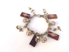 This wood block charm bracelet measures 7. There are 12 charms attached to the double link chain that closes with a working fold over clasp.