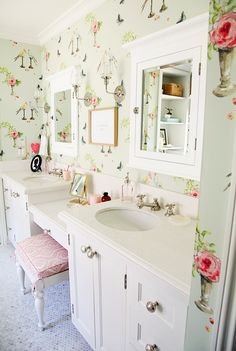 Bathroom with light green patterned wallpaper, white counters, white cabinet mirrors, glass and silver light fixtures, light tile floors, and white stool with pink patterned cushion