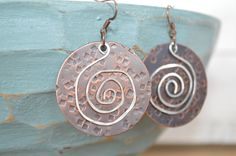 Welcome!    These Hammered copper earrings are antiqued and accented with a hammered silver spiral. They have 1 1//2'' circle discs.     All my earrings come packaged in a box and are ready to be given as a gift. To your friend, to you family... or to yourself!!    Like my Facebook page and message me to receive a coupon code for %10 off your total purchase   https://www.facebook.com/twistingtree/    Rogue Valley Locals** message me for discount shipping options. | Shop this product here…