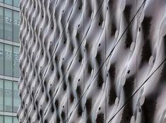 El acero corrugado posee unas perforaciones irregulares que por la noche, al interactuar la luz con ellas, generan efectos cinéticos que convierten al edificio en una estructura dinámica y en todo un hito urbano