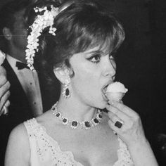 Gina Lollobrigida wearing the Bulgari Seven Wonders emerald necklace, as well as matching emerald and diamond earrings and ring, at the 1966 Corbis Monaco Ball, eating ice cream like the diva she is. Discover the history of Bvlgari in a consice way like no other and experience amazing jewels: http://www.thejewelleryeditor.com/jewellery/bulgari-history-of-style-celebrities-iconic-design/ #jewelry
