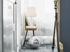Lampa na korkové stoličce vedle postele s bílým povlečením, upředu diskotéková koule. A jaká je vaše ložnice snů?