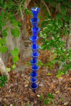 "garden art from tops of bottles over rebar ""planted"" in the ground and stacked    Must do and must get more blue beer bottles.  I think 3 or 5 of these would be stunning in the garden.  I want a finial of some kind on top though in another color...hmmmm"