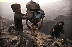 Bokapahari, India: A young woman stumbles as she tries to carry a large basket of coal