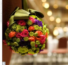 Two pomanders of brightly colored spring flowers adorned each end of the first pew, designating it as reserved seating for the families of the bride and groom.