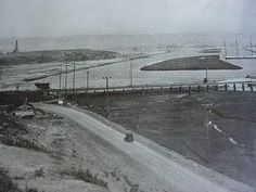 "Newport Beach in 1925, traveling South on the ""coastal route"" towards raised Newport Ave. Lido Isle in the foreground and a large 3 masted Schooner in the harbor."