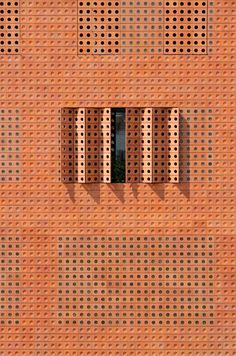 The brick, which has circular glass inserts, was used across the building's facades where it creates geometric patterns broken up by narrow window slits. Space Architecture, Amazing Architecture, Contemporary Architecture, Architecture Details, My Building, Building Facade, Brick Facade, Brick Wall, Types Of Bricks