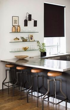 Industrial modern kitchen with b&w, gold accents, metal structure, and some delicate glass shelves at eye level to soften the feel.