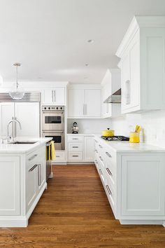 White Kitchen with Yellow Decor. White kitchen features two of clear glass globe light pendants illuminating a white island fitted with sink paired with modern gooseneck faucet beside stainless steel dishwasher topped with white quartz countertop. White shaker cabinets are paired with white quartz counters and white linear tile backsplash flanking stainless steel kitchen hood oak floor with Minwax Dark Walnut Stain. Clean Design Partners.#WhiteKitchenYellowDecor #WhiteKitchen…