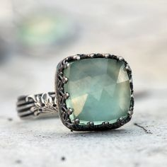 This is an amazing cushion and faceted cut prehnite set in sterling silver.  This is a gorgeous light green color and is large and bold.  It has an interesting setting with lots of detail.  The band also has a leaf detail that is feminine yet striking.The focal of this ring measures 1.5 cm square.  All of the sterling has been given a dark patina and the brush polished and tumbled for strength, dimension and to highlight the stunning details.  A gorgeous and showy ring.