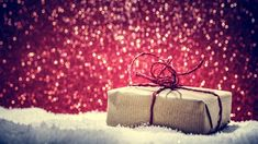 Retro rustic Christmas gift present in snow on glitter background by Photocreo